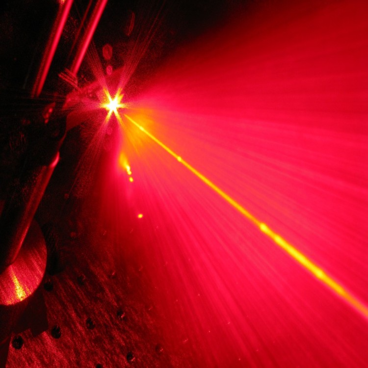 A random laser flash of light. A random laser (red) shines light in all direction while it is pumped by a standard unidirectional laser (yellow).