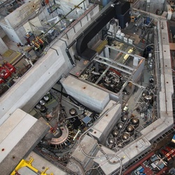 Huge lab to measure tiny proton. Top view of the laboratory, the <i>accelerator hall</i>, at Paul Scherrer Institute. The proton experiment is in the lower left corner, where we see the curved <i>muon extraction channel</i>, which transports the muon beam from the cyclotron trap to the target.