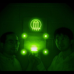 Shedding light in the dark. Zhengwei Pan and Feng Liu stand in a darkened room, using nothing but their recently invented ceramic discs that emit infrared light as a source of illumination. The image was taken using a digital camera with a night vision monocular. Their phosphorescent material was also mixed into the paint that was used to create the UGA logo behind them. There is no other source of illumination in the room; without the aid of a night vision device, the image would be completely dark.